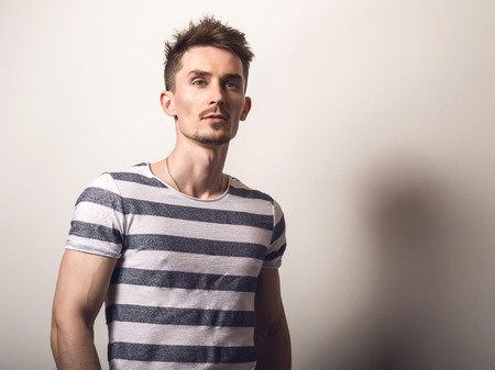Handsome young man in striped shirt pose against gray studio background. Stock Photo