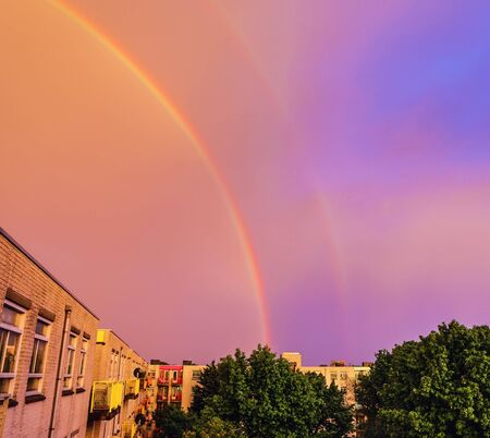 Double rainbow in evening sky above house. Editorial