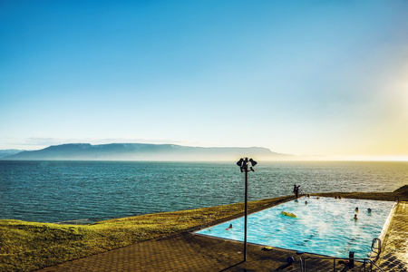 inground: Iceland pool on rock against beautiful sun set. Stock Photo