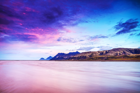 Picturesque landscape of a mountain river with traditional nature of Iceland at amazing sun set. Stock Photo