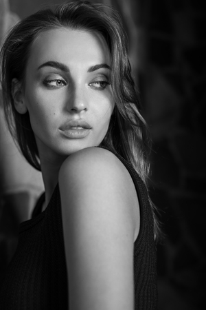 Elegant young beauty woman in interior black-white portrait.