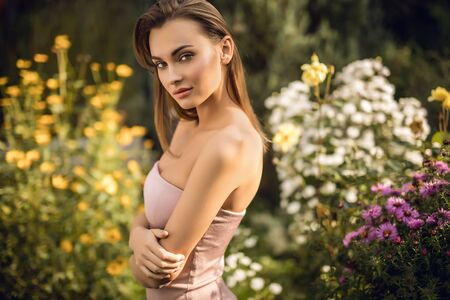 Outdoors portrait of beautiful young woman in casual clothes posing in autumn garden.