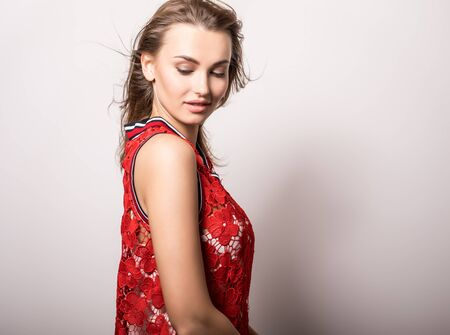 Young sensual model woman in red pose in studio. Banque d'images