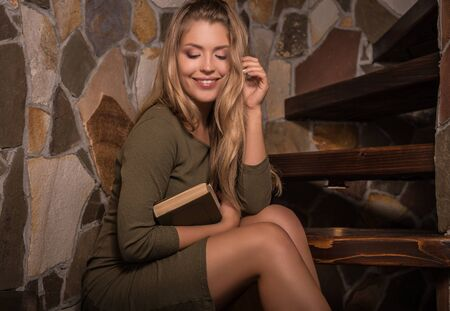 Young smiling beauty woman with books against house interior.