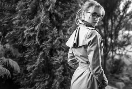 Outdoors black-white portrait of beautiful young woman in glasses against autumn garden. Banque d'images