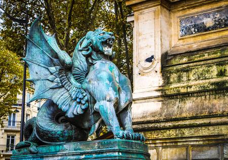 PARIS, FRANCE - NOVEMBER 11, 2017: Famous city sculpture sight and ancient architecture of Paris at rainy autumn evening on Paris, France in November 11,  2017
