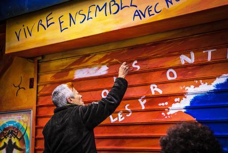 PARIS, FRANCE - NOVEMBER 11, 2017: Man drawing something at his shop wall at rainy autumn evening on November 11 in Paris - France.