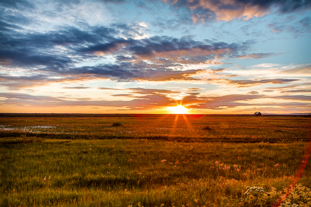 Picturesque landscape of a meadow with traditional nature of Iceland with amazing red sun set.