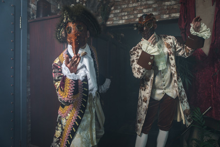 Actors in steam punk masks and antique costumes indoor.