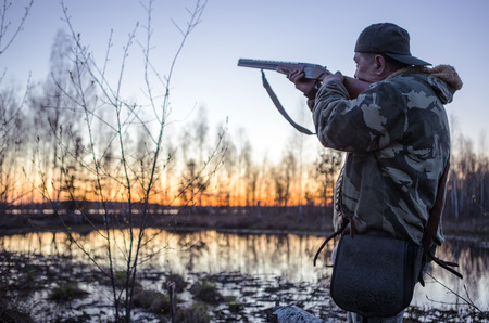 Hunter with a gun tracks down ducks on the river. 版權商用圖片 - 101339576