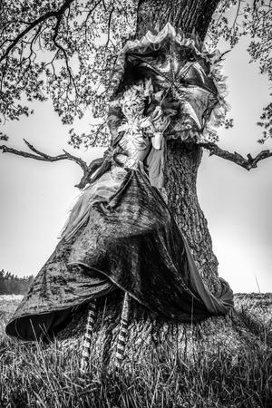 Fairy tale woman on stilts in fantasy stylization. Fine art black-white photo.