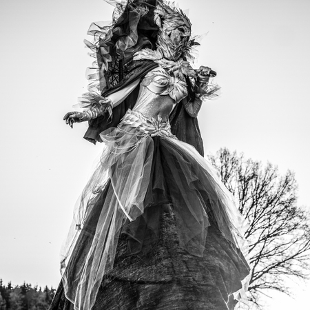 Fairy tale woman on stilts in fantasy stylization. Fine art black-white photo.