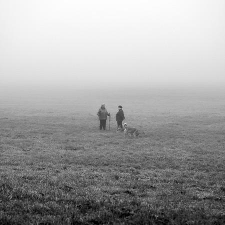 KRAKOW, POLAND - OCTOBER 18, 2018: Women with dogs walking in foggy Krakow park.