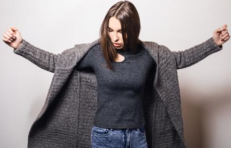 Beautiful young girl in gray coat posing in studio.