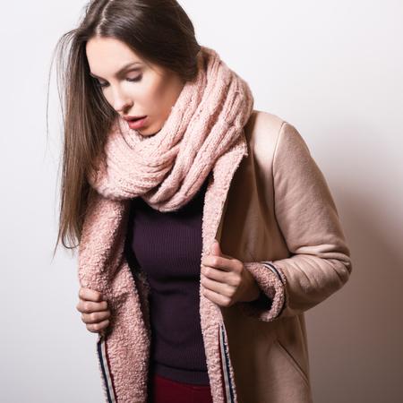 Beautiful young girl in pink coat posing in studio.