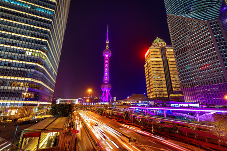 SHANGHAI, Ð¡HINA - APRIL 03, 2019: Modern central streets of Shanghai and high-rise buildings at night time.