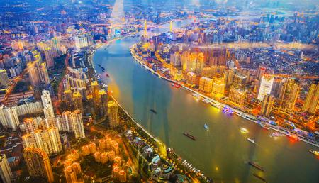 SHANGHAI, Ð¡HINA - APRIL 03, 2019: Top view of evening Shanghai from skyscraper through window glass.