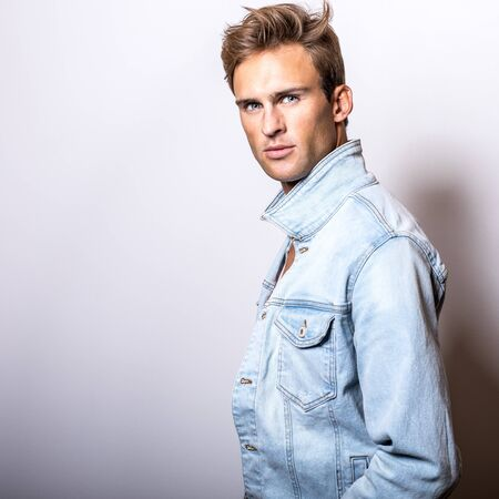 Handsome young man in jeans jacket pose in studio.