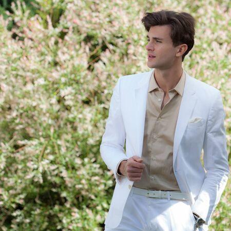 Hombre guapo elegante joven posando afuera.
