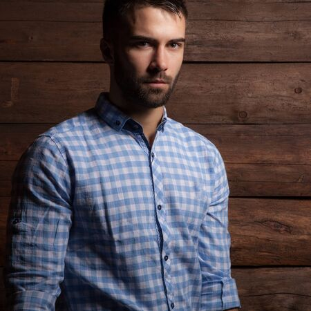 Portrait of handsome young man on wooden background. Stock Photo