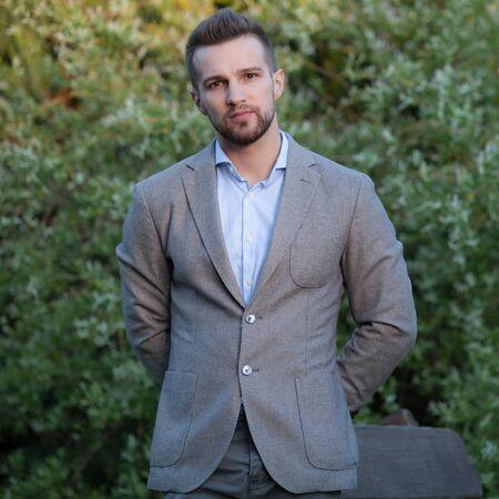 Young elegant handsome man posing outside.