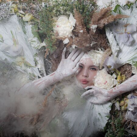 Female portrait in fairy tale stylisation surrounded with natural plants and flowers. 版權商用圖片