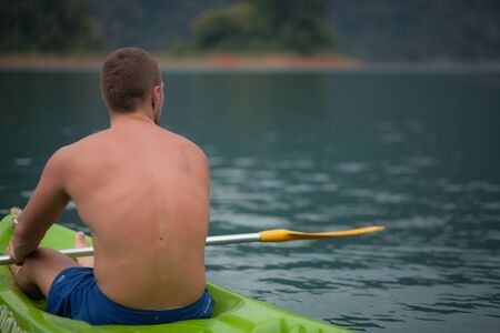 Young sports man is kayaking in lake.