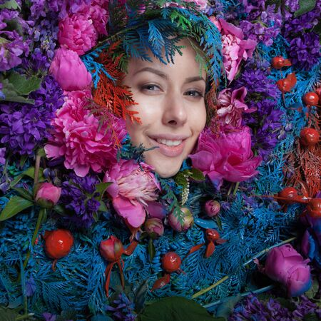 Female portrait in fairy tale stylization surrounded with natural flowers. Stock fotó