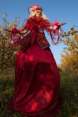Sensual blond girl in fantasy red fairy tale stylization in apple park.