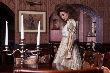 Victorian stylized fashion model in antique interior.