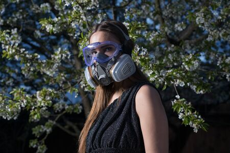 Young beautiful girl portrait in a mask with degree of protection posing in twilight of spring garden.