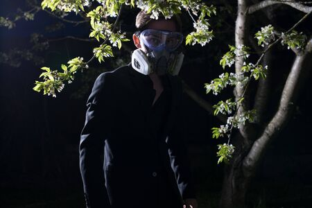Young man portrait in mask with degree of protection posing in twilight of spring garden.