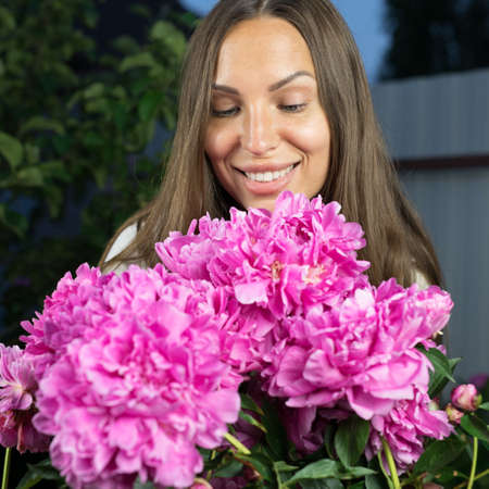 Young girl in evening garden enjoys bouquet of pink peonies. 스톡 콘텐츠
