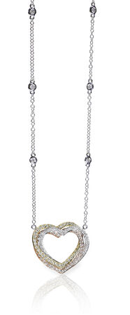 A beautiful diamond and gold heart pendant dangles from a chain. Fine Jewelry necklace isolated on a white background with shadow and reflection