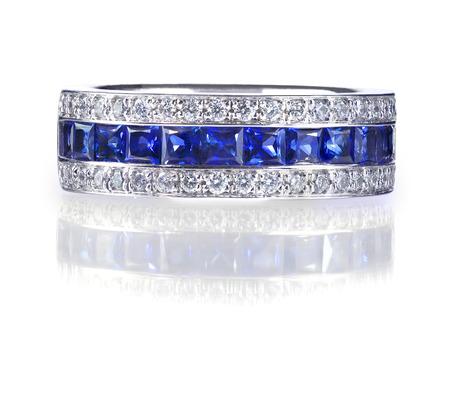 Un anneau de pierre gemme bleue mis en or avec des diamants. Isolé sur blanc avec une réflexion.