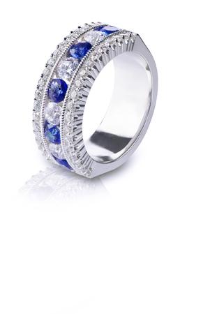 zafiro: Un anillo azul de la piedra preciosa fijó en oro con diamantes. Aislado en blanco con una reflexión.