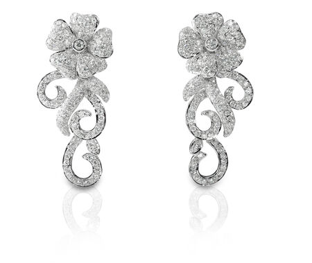 Beautiful floral shaped Diamond pave earrings isolated on white with a reflection photo