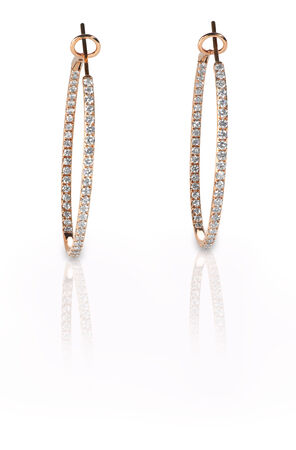 Pierced diamond hoop earrings in rose gold isolated on a white background with reflection