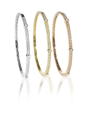 Set of three colored gold diamond bangle bracelets standing upright isolated on white with a reflection 版權商用圖片 - 27942990