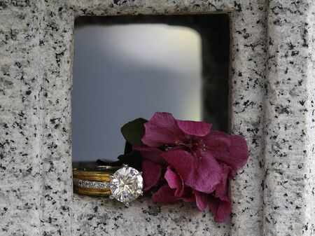 round brilliant: Diamond Wedding Engagement Ring Styled Next to Flower. Round brilliant large diamond with cherry blossom pink blooms