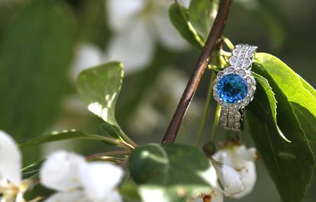 Blue topaz diamond engagement wedding ring nestled on a branch