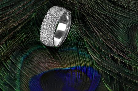 Diamond wedding ring on feathers Фото со стока