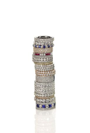 Diamond gemstone rings stacked together bridal wedding and engagement setting isolated on white Foto de archivo