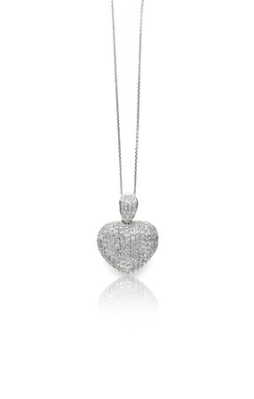 A beautiful heart shaped pave diamond and white gold or silver pendant dangles from a chain. Fine Jewelry necklace isolated on a white background with shadow and reflection
