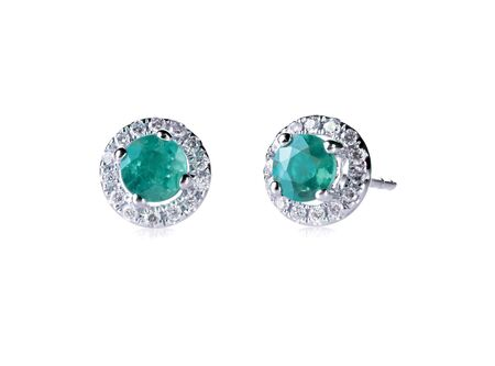 Round emerald diamond stud earrings in a halo setting isolated on white