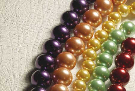 Multiple strands of colored pearls on a textured background 版權商用圖片