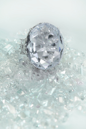 Beautiful large diamond engagement wedding ring sitting on multiple loose diamonds scattered throughout the background