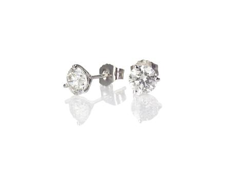Orecchini a perno con diamanti fine gioielli rotondi brillanti orecchini forati isolati su bianco con una riflessione Archivio Fotografico
