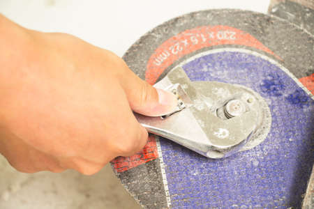 The repairman replaces the disk with a key at the angle grinder Banco de Imagens