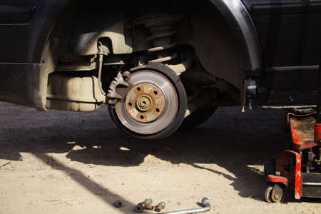 Wheel replacement on new black sedan car, jack holds the body in the raised position Stock Photo